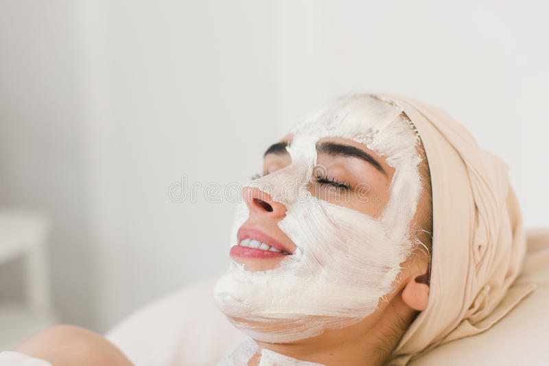 Woman with facial clay mask. Spa beauty organic facial mask application at day spa salon. Woman applying facial clay mask at spa salon, side view royalty free stock photo