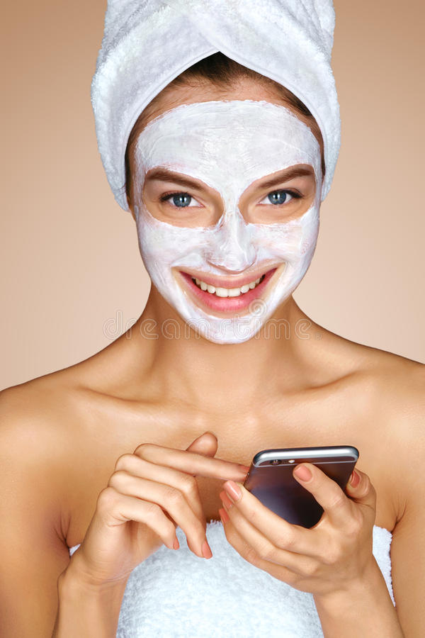 Woman with facial mask using cell phone royalty free stock images