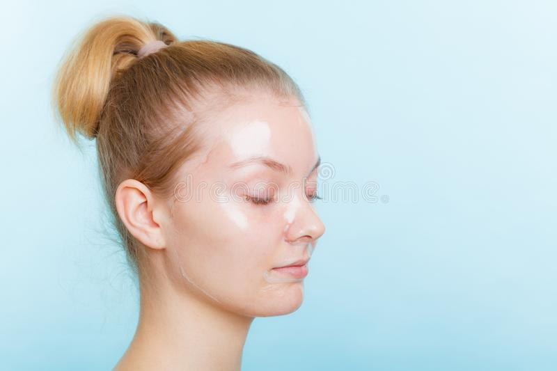 Woman in facial peel off mask. Young woman in facial peel off mask. Peeling. Beauty and skin care. Side view royalty free stock photography