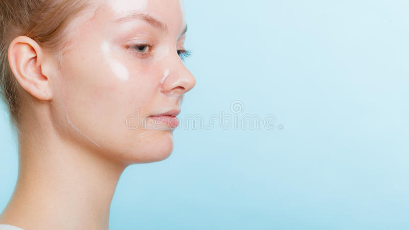 Woman in facial peel off mask. Young woman in facial peel off mask. Peeling. Beauty and skin care. Side view royalty free stock image