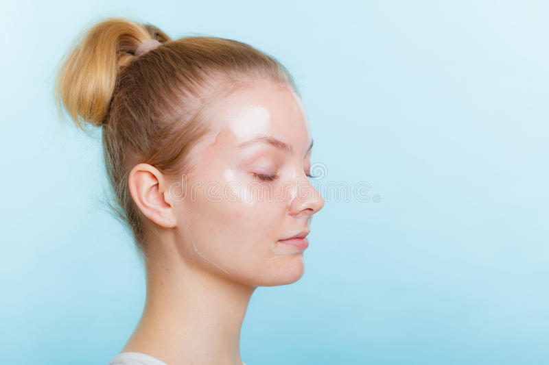 Woman in facial peel off mask. Young woman in facial peel off mask. Peeling. Beauty and skin care. Side view stock photos