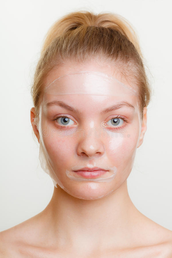 Woman in facial peel off mask. Young woman in facial peel off mask. Peeling. Beauty and skin care. Studio shot on gray stock image