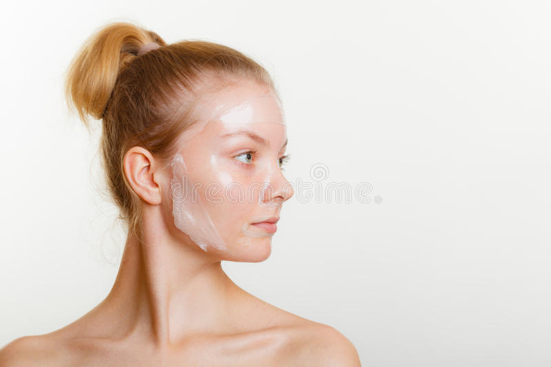 Woman in facial peel off mask. Young woman in facial peel off mask. Peeling. Beauty and skin care. Studio shot on gray royalty free stock photo
