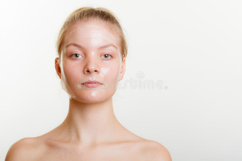 Woman in facial peel off mask. Young woman in facial peel off mask. Peeling. Beauty and skin care. Studio shot on gray royalty free stock images