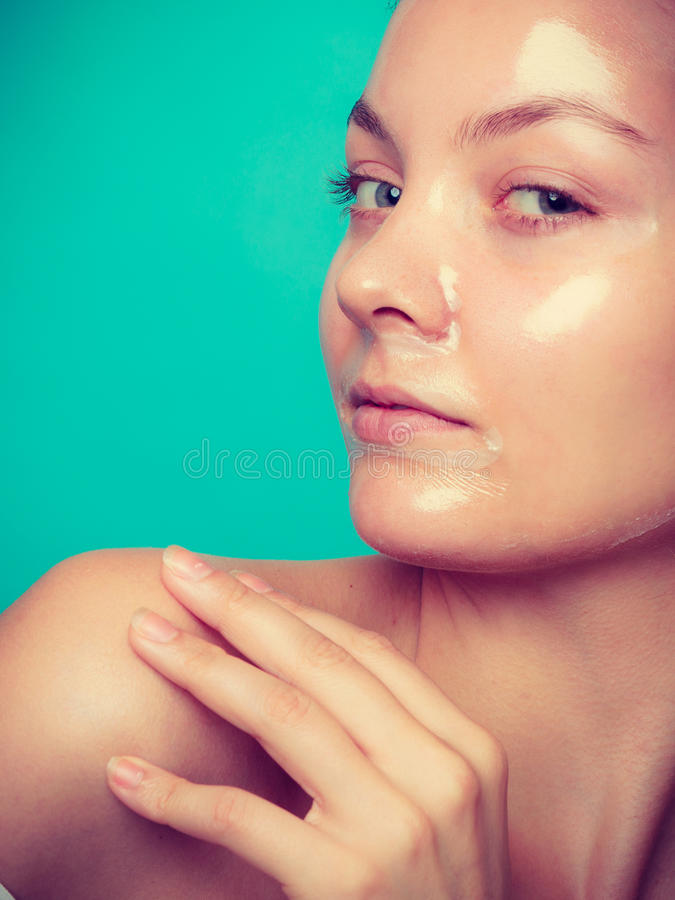 Woman in facial peel off mask. Young woman in facial peel off mask. Peeling. Beauty and skin care. Studio shot on green stock photography