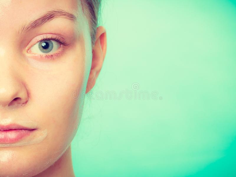 Woman in facial peel off mask. Young woman in facial peel off mask. Peeling. Beauty and skin care. Studio shot on green stock photos