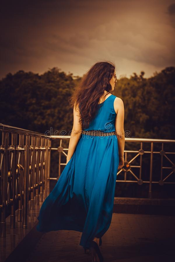 Woman Facing Away Wearing Blue Tank Long Dress Looking Out to Trees royalty free stock photography