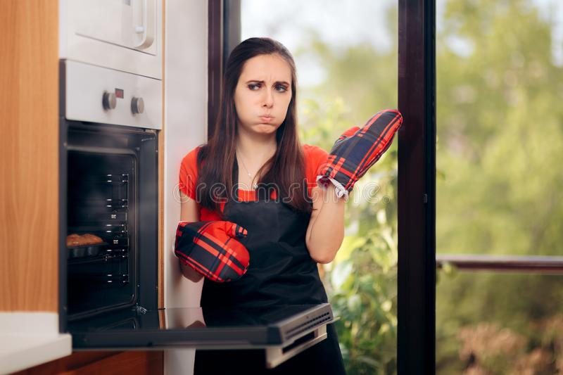 Woman Failing at Baking Some Muffins in the Oven royalty free stock photo