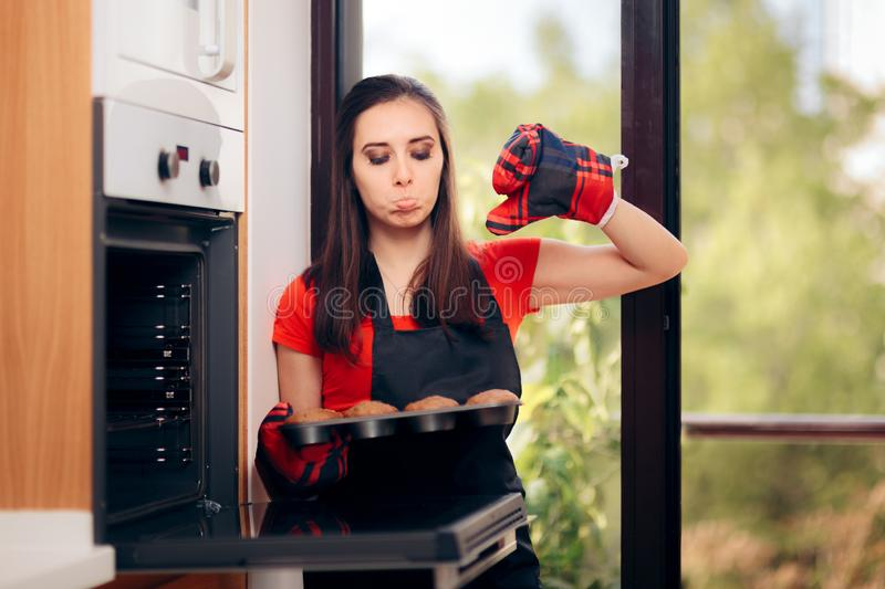 Woman Failing at Baking Some Muffins in the Oven stock photo