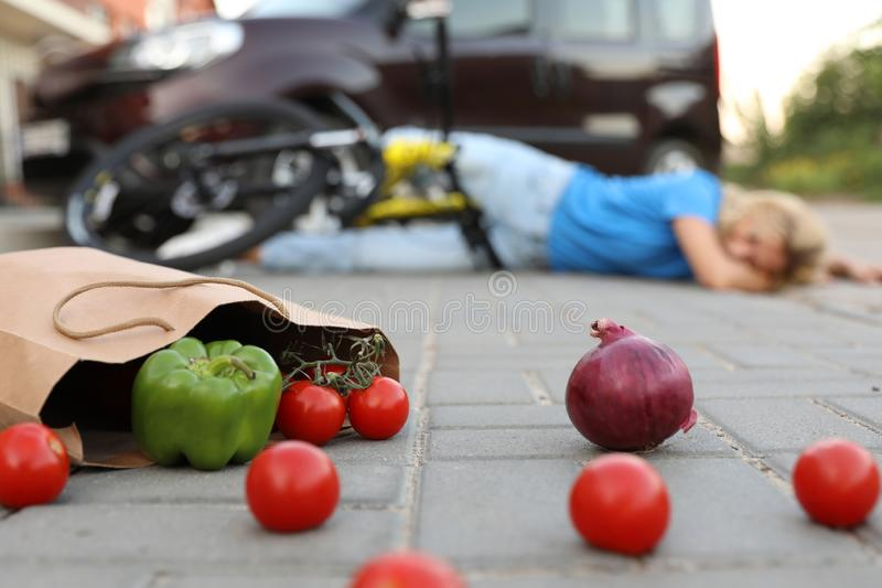 Woman fallen from bicycle after car accident, focus on scattered vegetables royalty free stock image