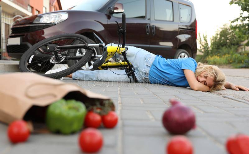 Woman fallen from bicycle after car  and scattered vegetables on street. Woman fallen from bicycle after car accident and scattered vegetables on street stock photography