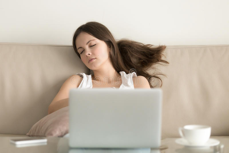 Woman falling asleep on sofa in front of laptop stock images
