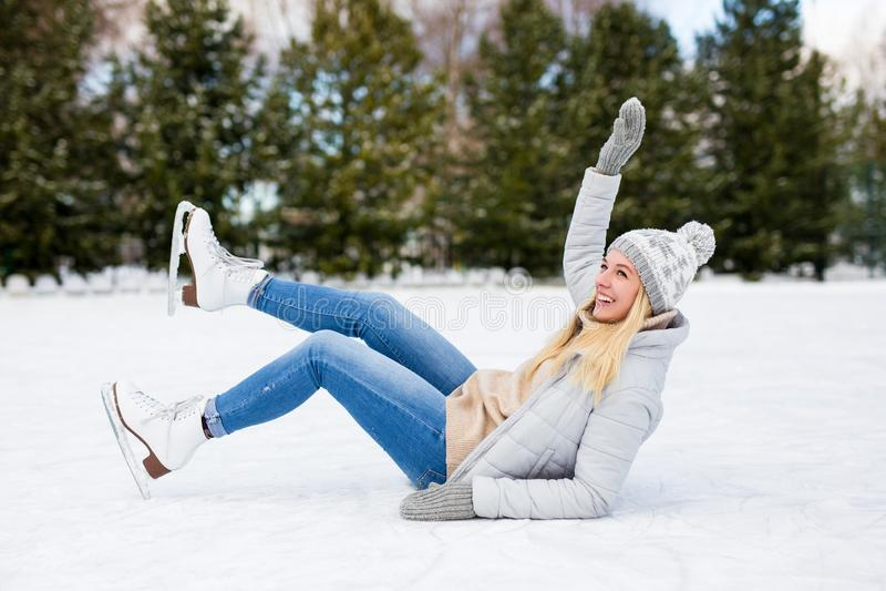 Woman falling down while ice skating at winter rink. Young woman falling down while ice skating at winter rink stock photos