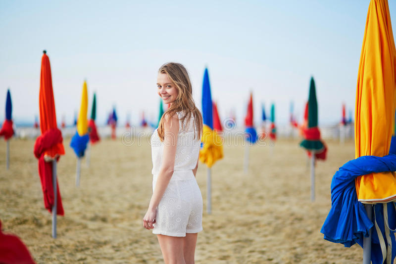 Woman with famous colorful parasols on Deauville Beach in France. Beautiful young woman with famous colorful parasols on Deauville Beach, Normandy, Northern stock photography