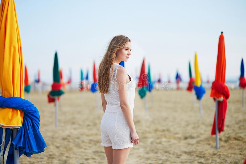 Woman with famous colorful parasols on Deauville Beach in France. Beautiful young woman with famous colorful parasols on Deauville Beach, Normandy, Northern royalty free stock images