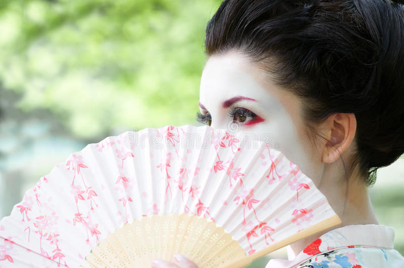 Woman with the fan, asian style portrait. Portrait of the beautiful young woman with geisha style makeup and the fan royalty free stock photography