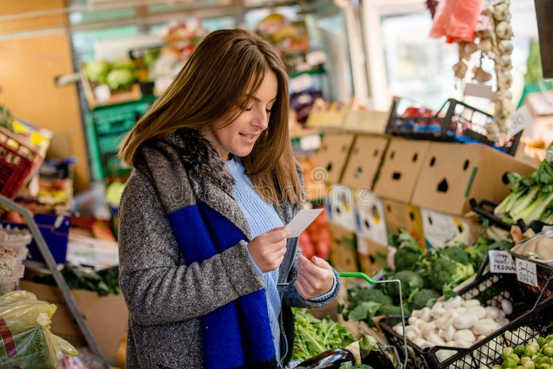 What else is necessary for today`s lunch?. Woman at farmer`s market, checking her shoping list royalty free stock photography