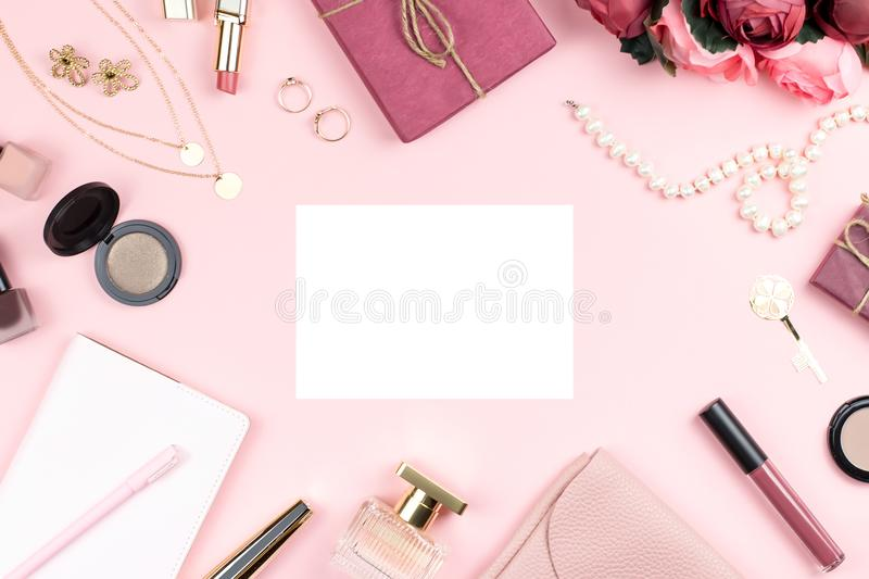Woman fashion accessories, flowers, cosmetics and jewelry on pink background, copyspace. Womens Day concept. Top view stock photography