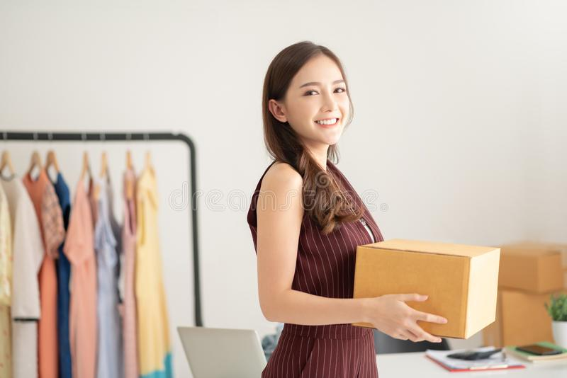Woman fashion designer standing and holding cardboard box. Portrait of Successful woman fashion designer standing and holding cardboard box. Startup, Business royalty free stock photography