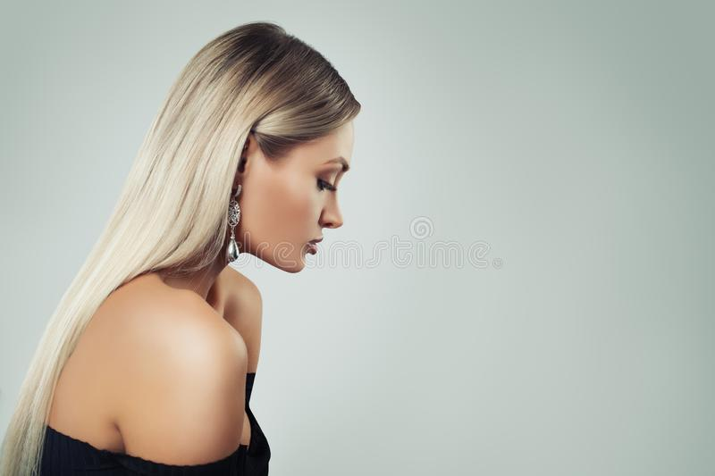Woman Fashion Model with Blonde Hair, Makeup and Black Pearls Earrings on Background with Copy space, Profile.  royalty free stock photo