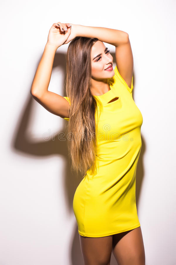 Woman fashion model standing in yellow dress against gray background royalty free stock photos