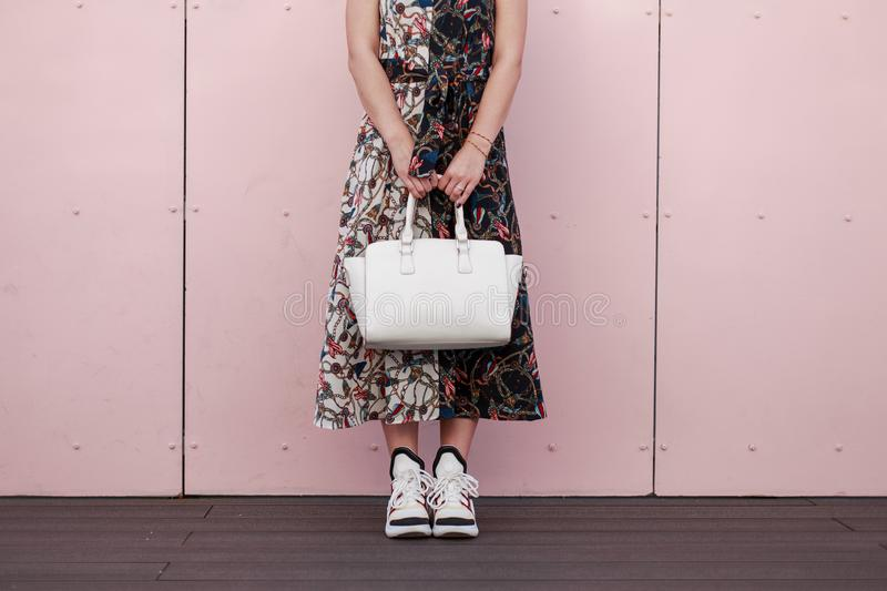 Woman in a fashionable dress with a white stylish bag stand royalty free stock images
