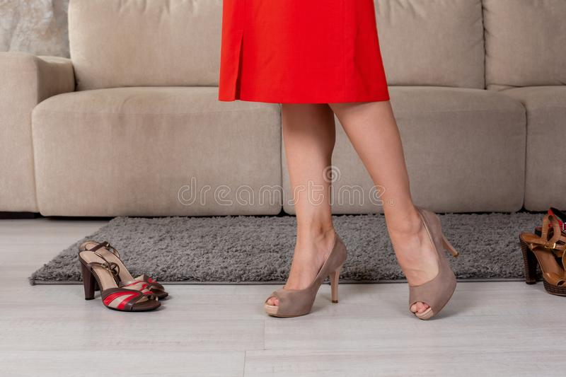 Woman in fashionable short dress skirt high heels standing nearn couch. stock image