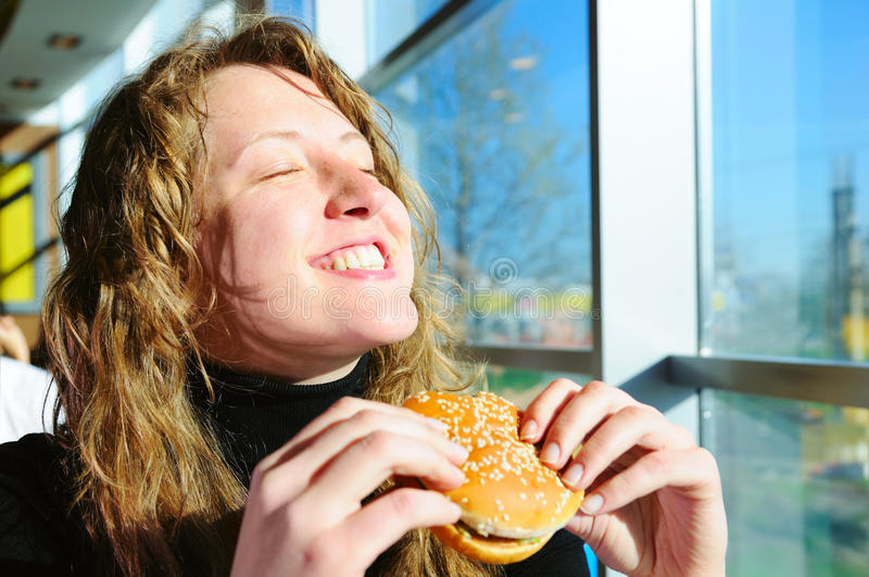 Woman in fast food cafe. Very happy woman is eating cheeseburger in fast food cafe stock photography