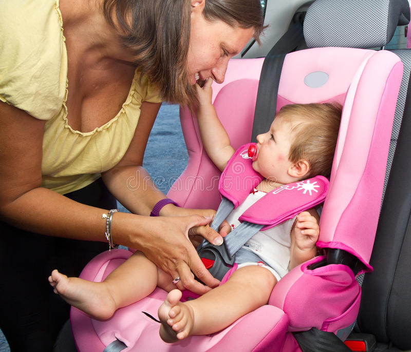 Woman fastening her son on a baby seat in a car stock photos