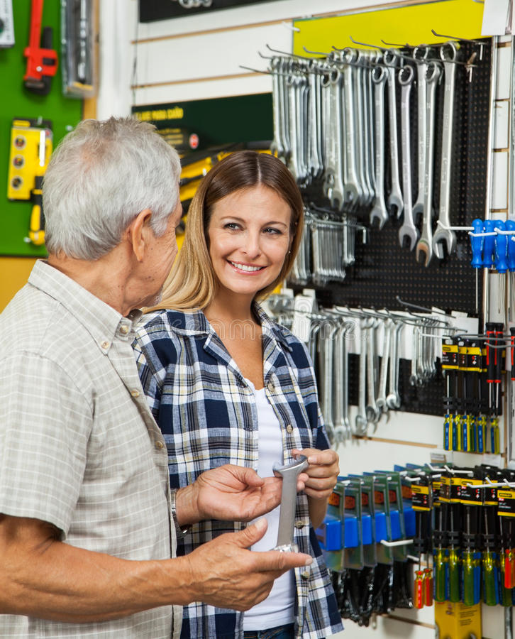Woman With Father Holding Wrench In Shop. Mid adult women with father holding wrench while standing in hardware shop stock photos
