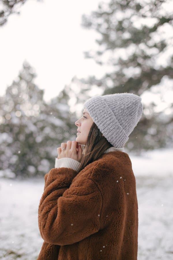 Woman in faux fur coat and woolen hat enjoying snowfall. Young beautiful woman wearing fashionable faux fur coat and woolen hat enjoying snowfall in a winter stock photography