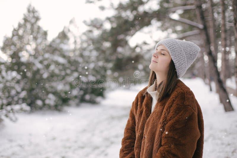 Woman in faux fur coat and woolen hat enjoying snowfall. Young beautiful woman wearing fashionable faux fur coat and woolen hat enjoying snowfall in a winter stock image