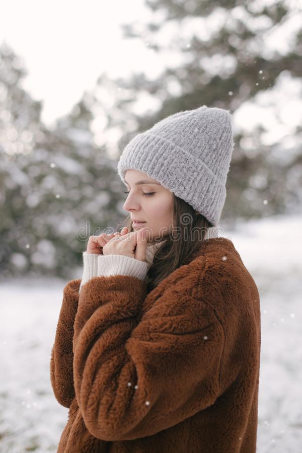Woman in faux fur coat and woolen hat enjoying snowfall. Young beautiful woman wearing fashionable faux fur coat and woolen hat enjoying snowfall in a winter royalty free stock photo