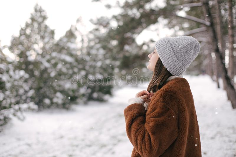 Woman in faux fur coat and woolen hat enjoying snowfall. Young beautiful woman wearing fashionable faux fur coat and woolen hat enjoying snowfall in a winter royalty free stock photos