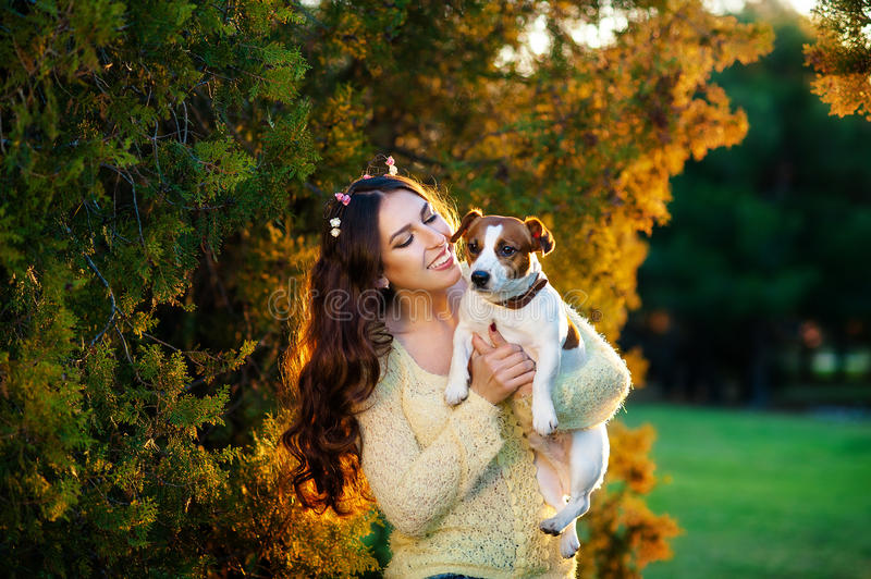 Woman with a favorite dog breed Jack Russell Terrier playing in the beautiful garden royalty free stock photography