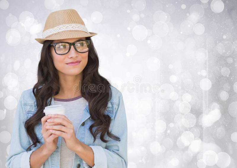 Woman in fedora with white coffee cup against white bokeh. Digital composite of Woman in fedora with white coffee cup against white bokeh stock photos