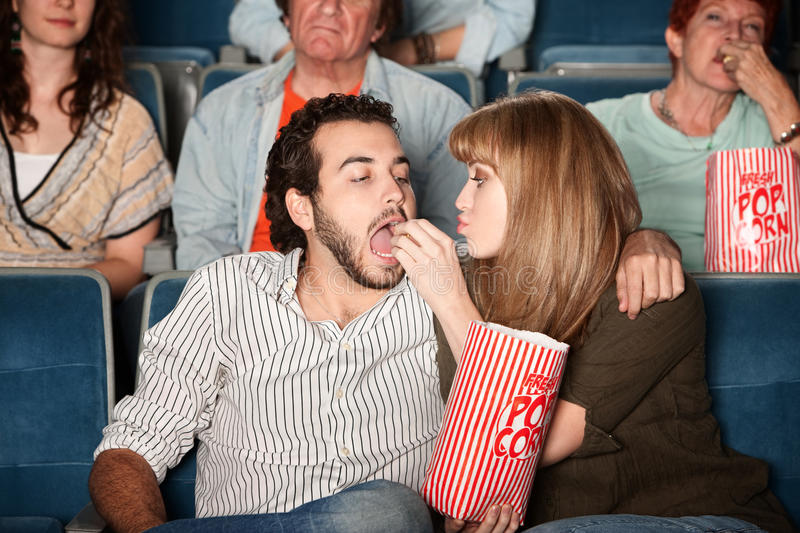 Woman Feeds Boyfriend At Movie Stock Images