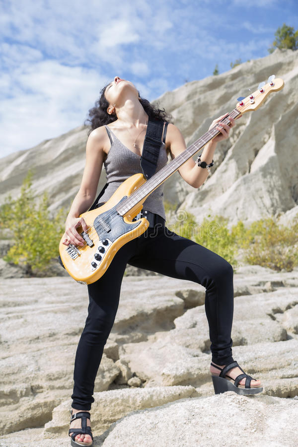 Woman feel great playing on bass guitar royalty free stock photos