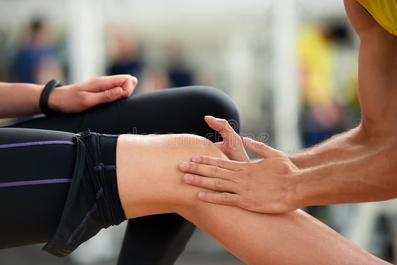 Woman feeling ache in knee after workout. Young women suffering from knee injury while exercising at sport club. Massage after workout stock image