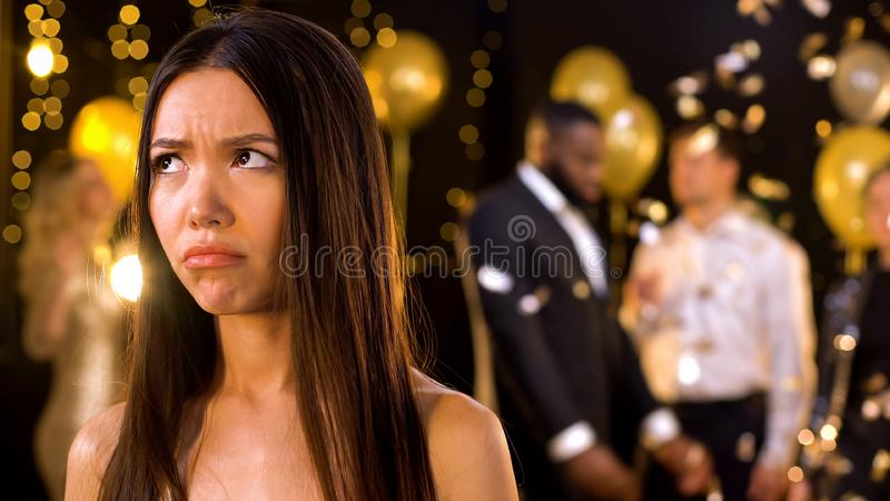 Woman feeling alone at party, dancing people on background, relations problems stock images