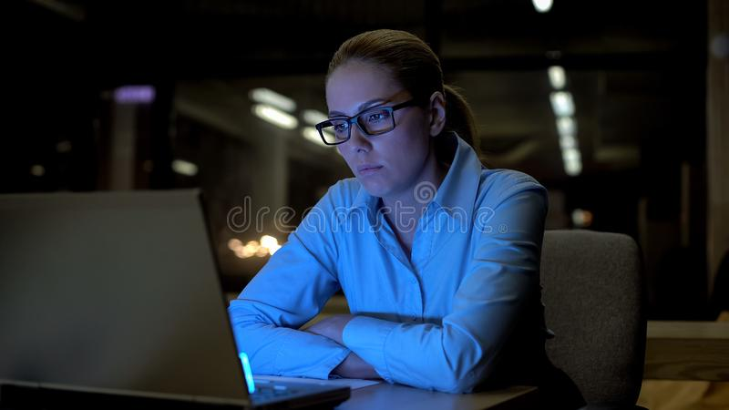 Woman feeling bored and exhausted in office, working overtime, low productivity stock photo