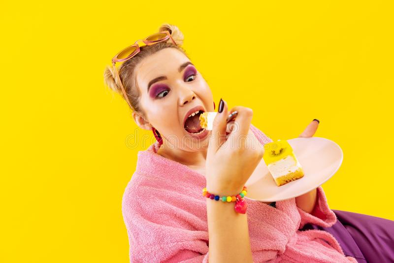 Woman feeling crazy while eating delicious sweet cake stock images