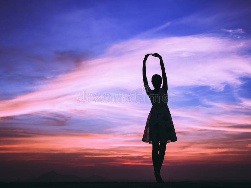 Woman feeling free at sunset. Silhouette of free woman enjoying freedom feeling happy at sunset. relaxing woman in pure happiness royalty free stock image