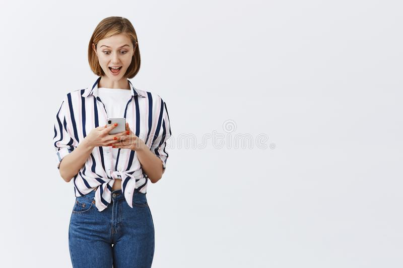 Woman feeling happy and over-emotive, receiving amazing and great news via internet, gazing pleased and impressed at stock images