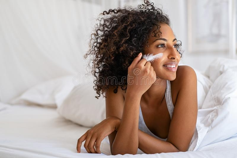Woman feeling her soft skin on bed stock images