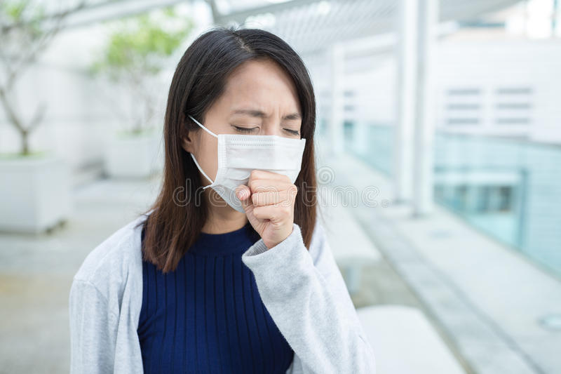Woman feeling sick and wearing face mask stock photos
