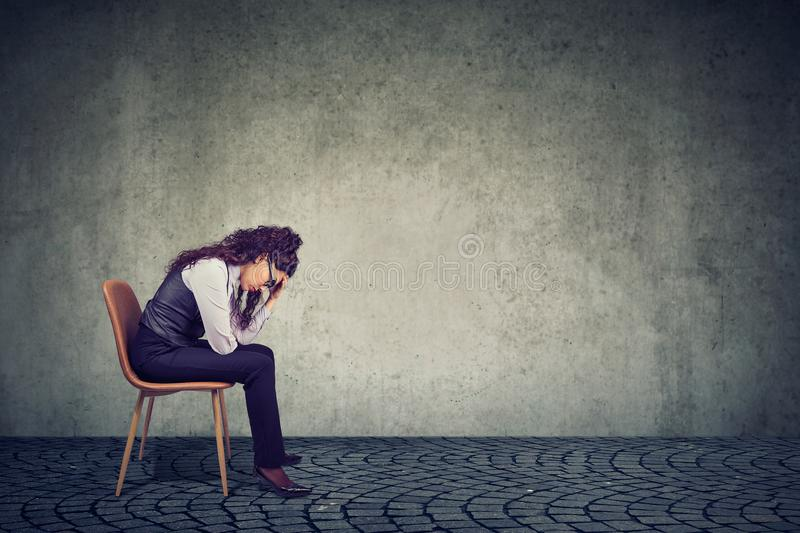 Woman feeling stress from work sitting on chair and looking down stock photo