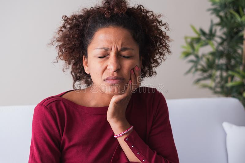 Woman feeling toothache and massaging gums. Black woman needs a visit to the dentist stock images