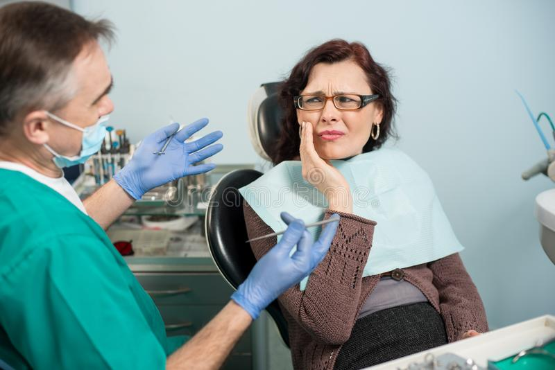 Woman feeling toothache, touching cheek with hand at dental clinic. Senior dentist trying to help. Dental care and health concept royalty free stock photography