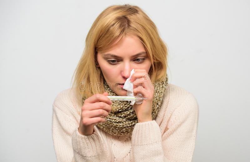 Woman feels badly ill sneezing. Girl in scarf hold thermometer and tissue close up. Cold and flu remedies. High. Temperature concept. Take temperature and stock photography